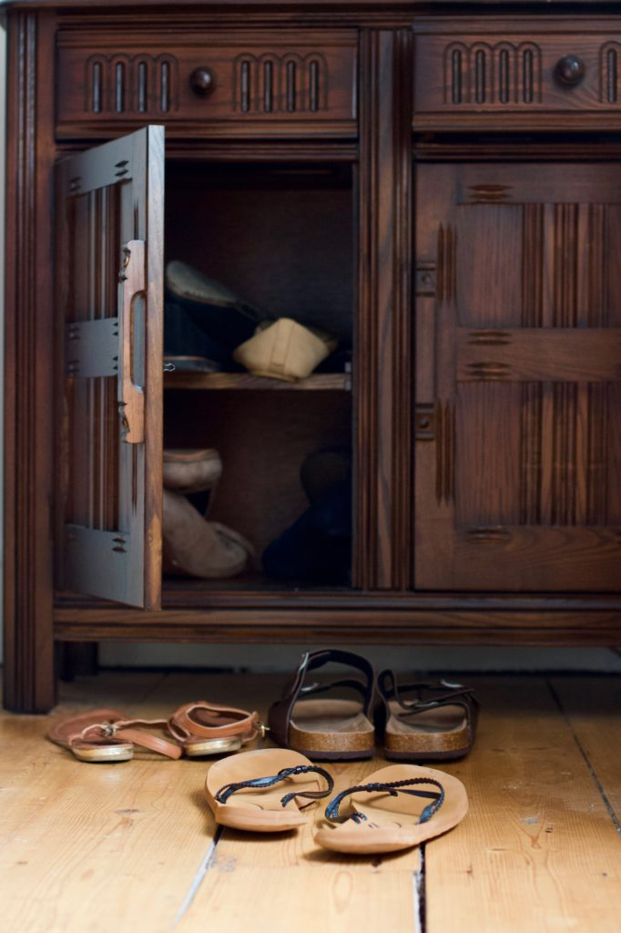 Two pairs of sandals and a pair of flip flops in front of a small dark brown wooden cabinet. The left hand cabinet door is open with more shoes visible inside.