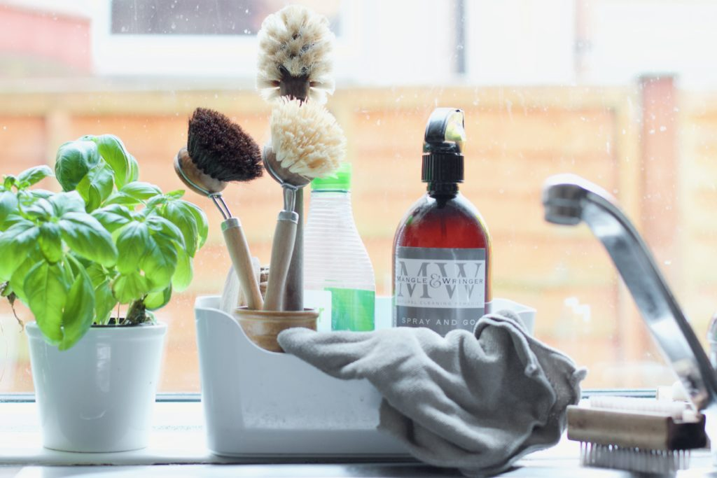A small white box behind a sink, three washing up brushes tugged in, plus a eco friendly washing up liquid bottle and a brown spray bottle. To the left is a small basil plant. To the right is a hand brush and the tap.