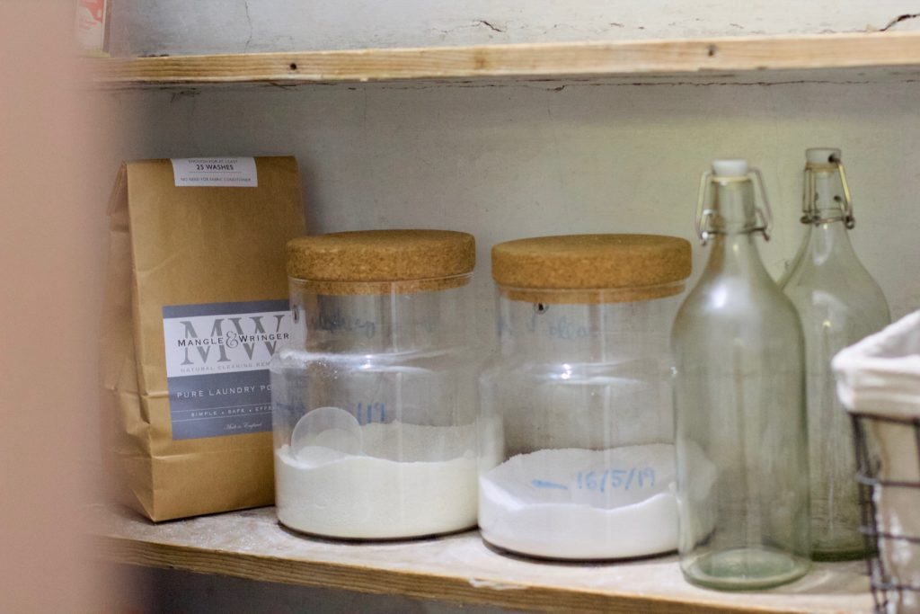 A door half open revealing a rough shelves with two big glass jars containing washing powder, two glass bottles next to it and a paper bag in the left corner.