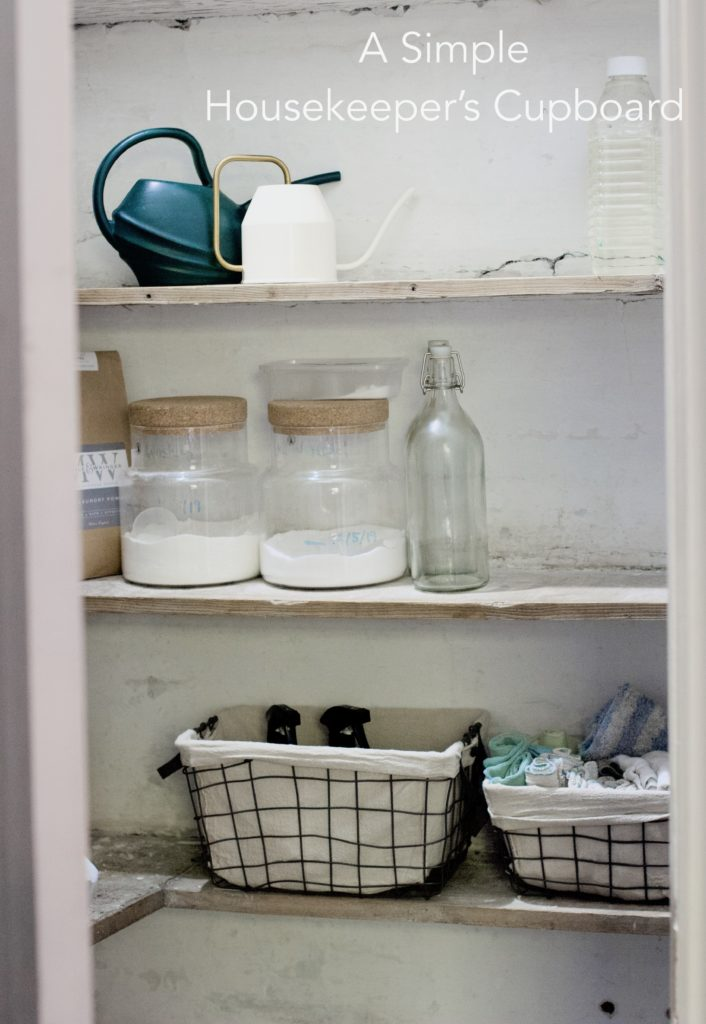 Open door revealing three shelves in a cellar entrance. Paint is peeling nd the plaster is cracked in parts. The top shelf holds two watering cans, white and green, to its left and a clear bottle with unidentifiable liquid. The middle shelf holds a brown paper bag, two glass containers with washing powder and two empty glass bottles. On the bottom shelf are two black wired baskets with soft beige inlays, some spray cans are peeking out as well as an assortment of cloths and towels.