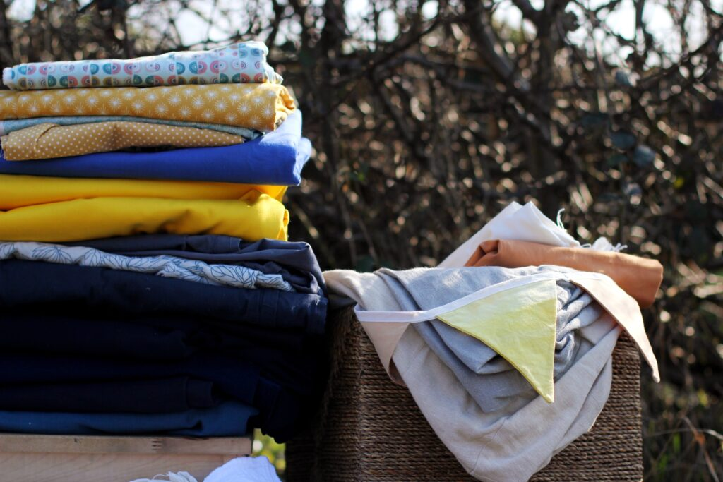 A stack of blue and yellow fabric to the left of the frame, with the top of a square basket visible next to it. Fabrics scraps in neutral colours are hanging out of the basket, as well as a few flags of a yellow and pink bunting.