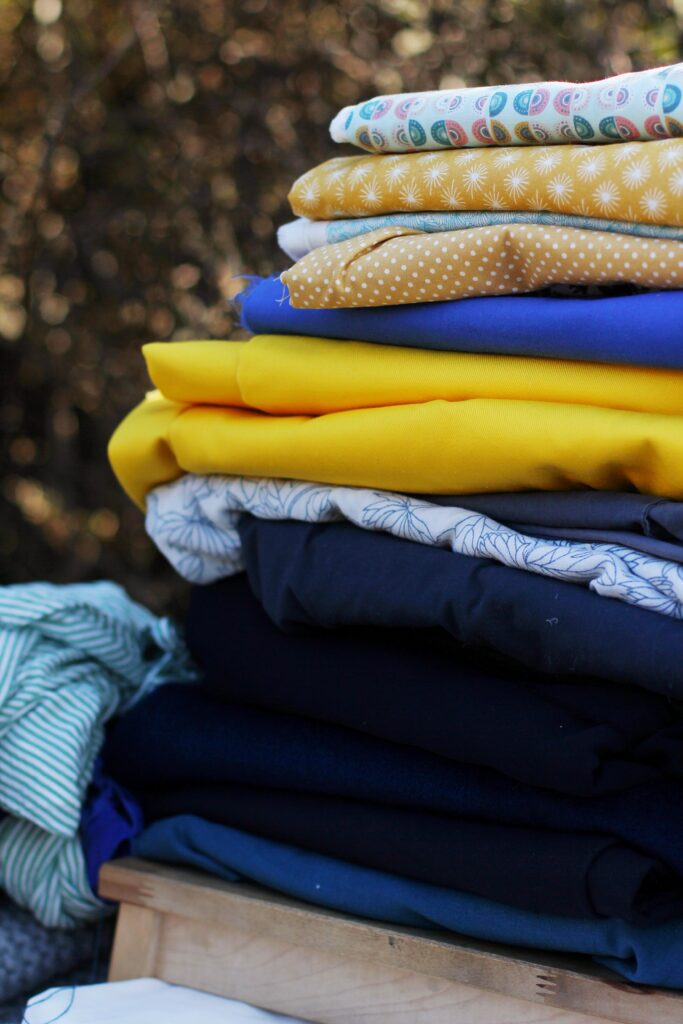 Close up of large stack of meter fabric. Mostly dark blue fabrics with a bright yellow cotton folded in the middle.
