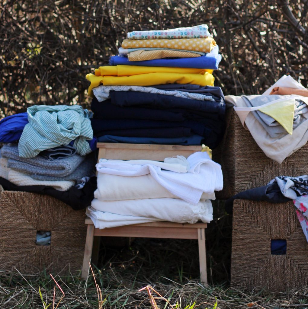 An assortment of different fabrics and garments in front of a bare hawthorn hedge. A small step stool in the centre holds folded white fabrics on the lower step, and blue and yellow meter fabric on the top. To the left and right are square baskets overflowing with garments and scraps.