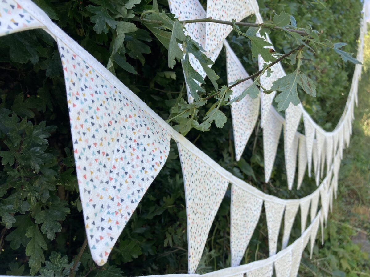 Four rows of buntings, white with tiny coloured triangles printed on, hung in a hawthorn hedge.